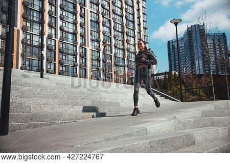 Joyous Sportswoman Jogging In A New Residential District