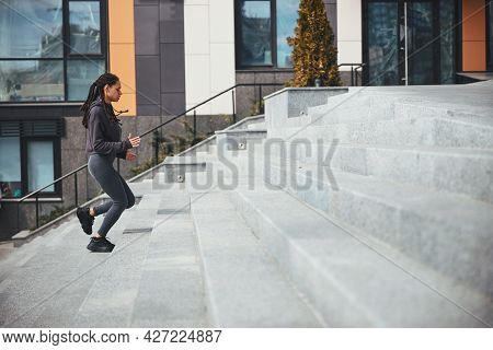 Sportswoman With Trendy Afro Bunches Ascending The Concrete Steps
