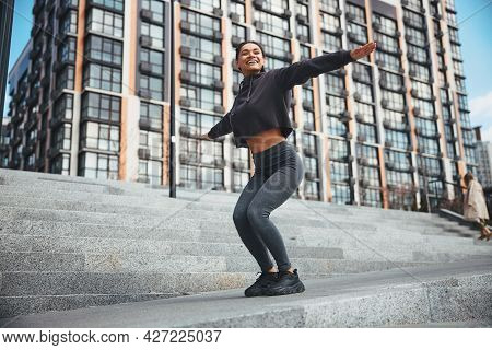 Pleased Sportswoman With Cornrows Squatting On The Concrete Stairs