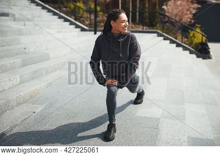 Smiling Sportswoman Doing A Warm-up Exercise Outdoors