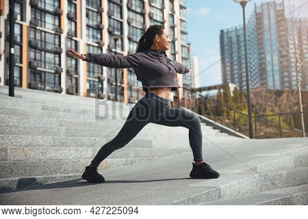 Pleased Lady Doing A Warm-up Exercise On The Concrete Stairs