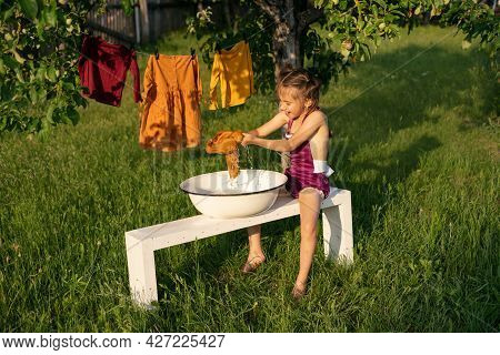 A Little Girl Washes Clothes With Her Hands In A Basin, Sitting On A Bench In The Garden. Laundry Is