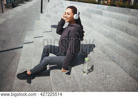 Happy Pretty Lady In Wireless Headphones Enjoying Her Favorite Music