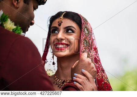 Indian Bridegroom Adjusting Headscarf On Happy Bride In Sari