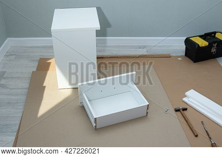Process Of Assembling Box For New White Bedside Table. Concept Moving And Buying New Furniture In Ap