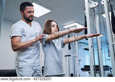 Pediatric Therapist Checks Posture Of Girl With Her Arms Stretched Forward In Rehabilitation Center