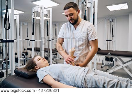Portrait Of Physiotherapist Massages Girls Hand In Physio Room. Professional Pediatric Therapist