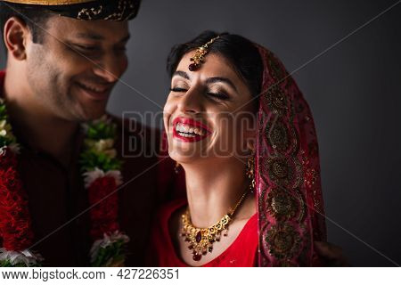 Blurred Indian Man In Turban Looking At Happy Bride In Traditional Headscarf Isolated On Grey