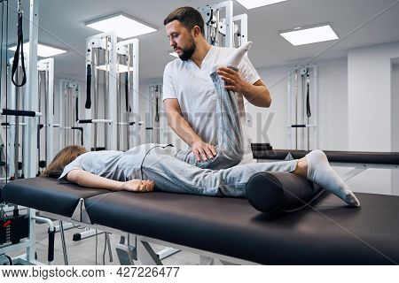 Physiotherapist Controlling Knee Of Patient In Bright Rehab Clinic Closeup. Massage Therapist