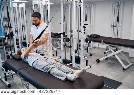 Physiotherapist Treats Girl In Rehabilitation Center On Elastic Machines. Chiropractor Treatments