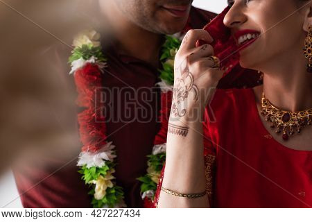 Cropped View Of Cheerful Indian Bride Touching Headscarf And Flirting With Bridegroom