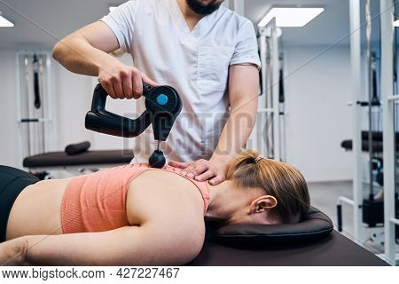Physiotherapist Treats Woman Spine And Back With Massaging Percussion Device. Physio Therapy