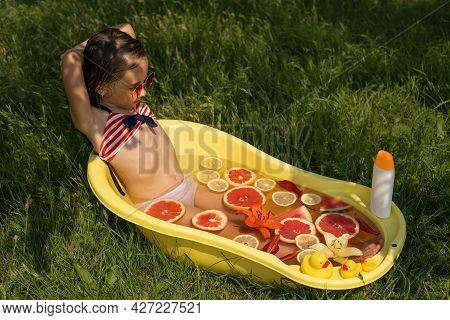 The Girl Is Enjoying Taking A Bath With Lemon, Grapefruit And Flowers In Nature Outdoors. Take A Bat