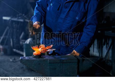 Professional Blacksmith In Uniform Using Heavy Hammer For Forging Molten Metal. Close Up Of String M