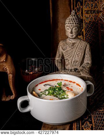 Very Good Tom Kha With A Base Of Coconut Cream, Mushrooms And Tofu Served In A Deep White Plate With