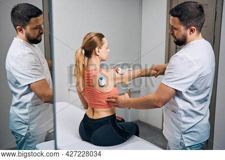 Physical Therapy Electrodes Myostimulation. Doctor In Uniform Puts Electrostimulator On Woman Hand