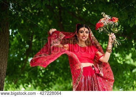 Happy Indian Bride In Red Sari And Traditional Headscarf With Ornament Holding Flowers