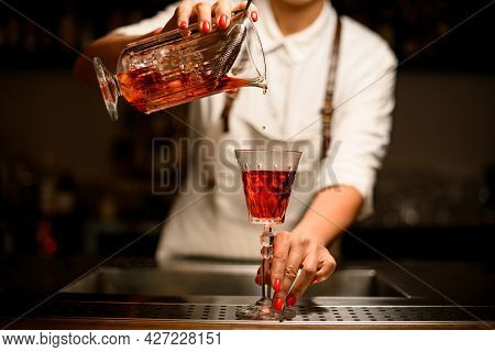 Great View Of Crystal Glass With Drink In Which Woman Bartender Pours Liquid