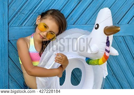 A Beautiful Girl In Yellow Sunglasses And A Swimsuit Is Standing By A Painted Blue Wooden Board Wall