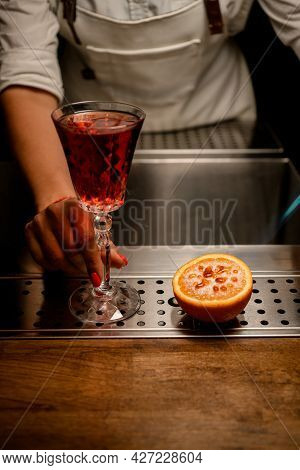 Crystal Glass With Drink And Half Orange With Burnt Caramel Crust On The Bar