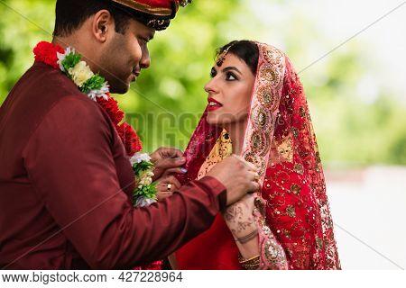 Indian Man Adjusting Headscarf On Bride In Sari