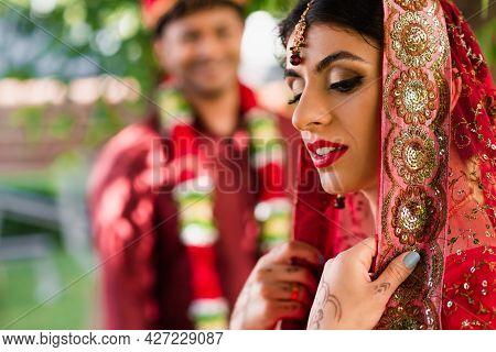 Indian Bride In Sari And Headscarf Near Blurred Man In Turban On Background