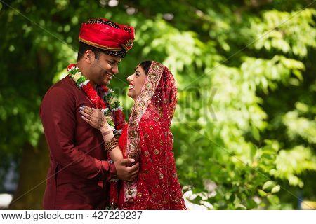 Happy Indian Man In Turban Hugging Joyful Bride With Mehndi In Sari And Headscarf