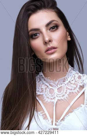 Beautiful Brown-haired Girl With A Perfectly Smooth Hair, And Classic Make-up. Beauty Face And Hair.