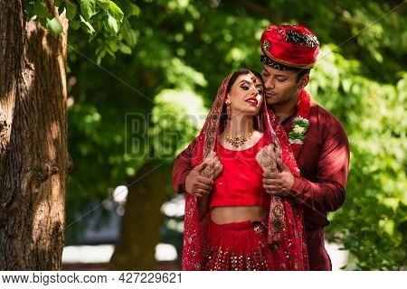 Indian Man In Turban Looking At Bride With Mehndi In Sari And Headscarf