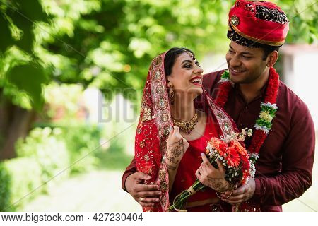 Happy Indian Married Couple In Traditional Wedding Clothes Looking At Each Other Outside