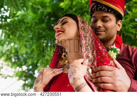 Low Angle View Of Pleased Indian Man In Turban Hugging Bride In Red Sari