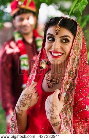 Joyful Indian Bride In Sari And Headscarf Near Blurred Man In Turban On Background