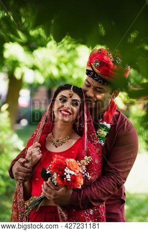 Happy Indian Man Hugging Cheerful Bride In Headscarf And Sari Outdoors