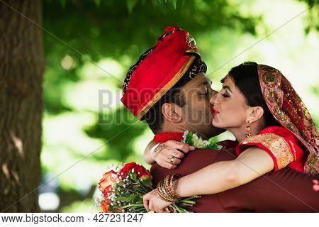 Indian Man In Turban Kissing Pretty Bride In Traditional Headscarf