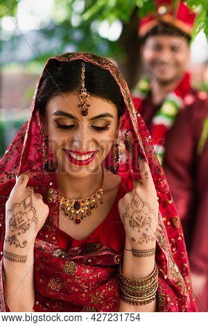 Cheerful Indian Bride In Sari And Headscarf Near Blurred Man In Turban On Background