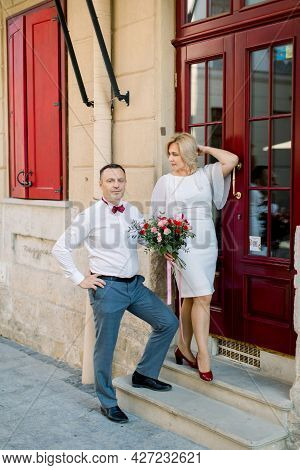 25th Wedding Anniversary. Happy Mature Loving Couple, Handsome Man With His Charming Wife In White D