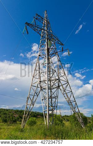 High-voltage Power Line Support Against Blue Sky At Sunny Summer Day. Industrial Background