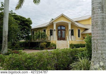 Exterior Of Generic Yellow And White Florida Home On A Cloudy Morning