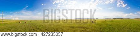 Russian Summer Panoramic Landscape With Sunny Green Meadows With Mown Hay, Haystacks And Awe Sky Wit