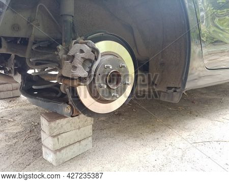 Close-up Of A Stolen Car Wheel With Brake Disk And Shaft Standing On A Bricks