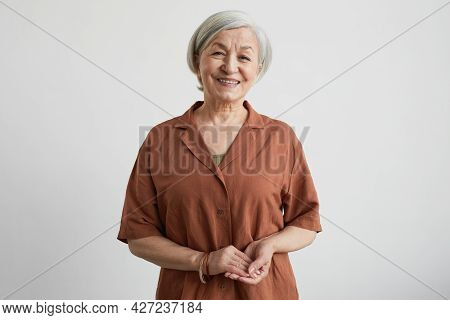Minimal Waist Up Portrait Of Modern Senior Woman Smiling At Camera While Standing Against White Back