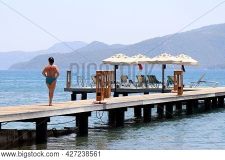 Beach Holiday On Sea Resort, Woman In Swimsuit Walking On Pier With Lounge Chairs And Parasols. Scen