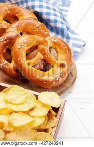 Fresh baked homemade pretzel with sea salt and potato chips on wooden table. Classic beer snack