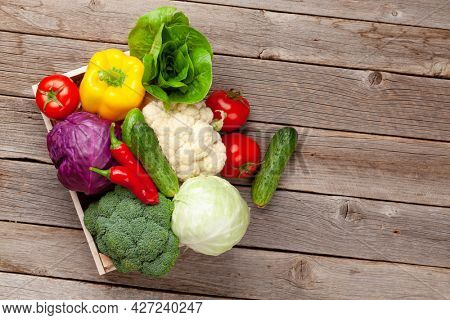 Various fresh vegetables in box on wooden table. Top view flat lay with copy space