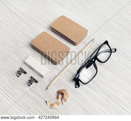 Corporate Identity Template. Blank Kraft Business Cards, Glasses, Pencil And Eraser On Light Wood Ta
