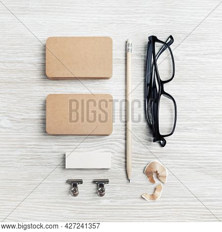 Kraft Business Cards, Glasses, Pencil And Eraser On Light Wooden Background. Top View. Flat Lay.