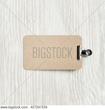 Blank Kraft Business Card And Clip On Light Wooden Background. Flat Lay.