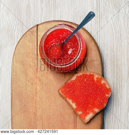 Fresh Delicious Caviar. Sandwich With Red Caviar, Glass Jar And Spoon. Flat Lay.