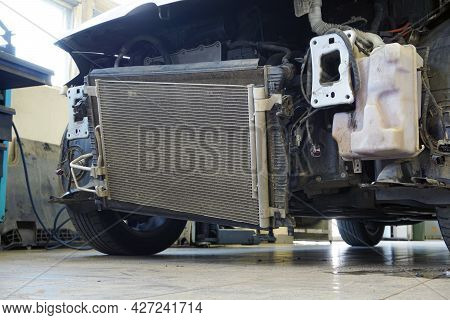 Modern Car In A Car Service. The Front Of The Machine Is Partially Disassembled. The Cooling Radiato