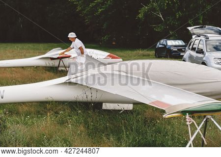 Man Prepares And Checks Gliders Parked In The Field, Ready To Fly. Small Aviation Extreme Sport Leis